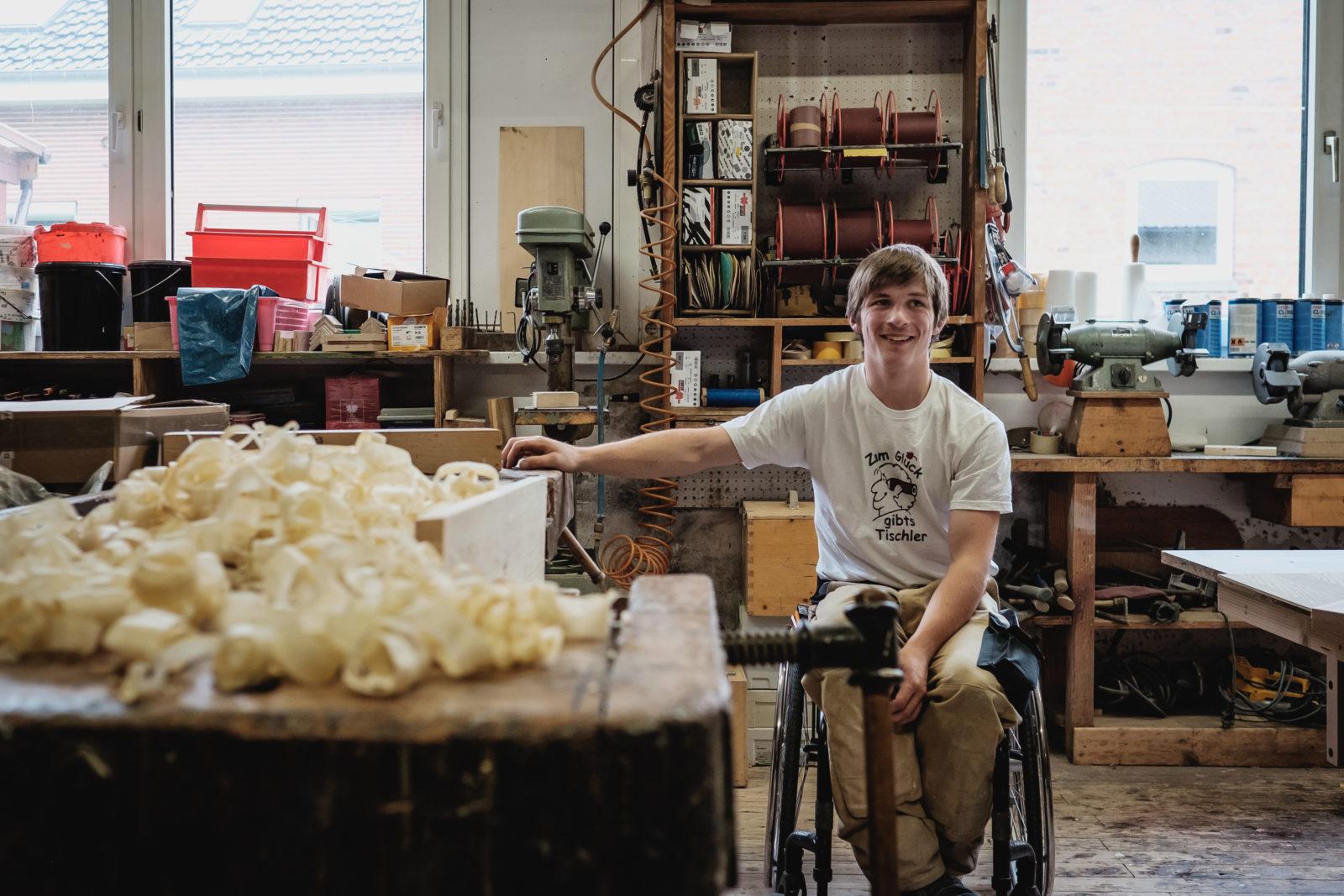 Ein junger Mann im Rollstuhl steht in der Tischlerwerkstatt.