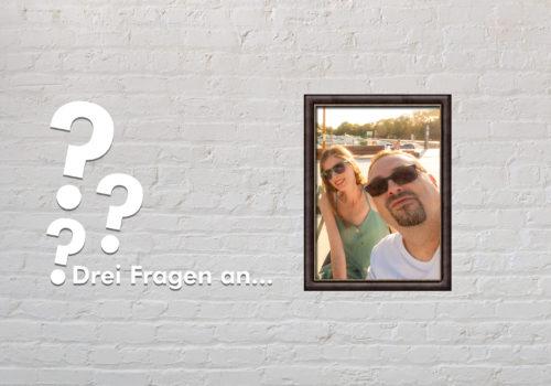 Fotomontage: Eine weiße Steinwand - darauf ein Rahmen, in den ein Bild von Adina und Timo Hermann montiert ist, daneben der Schriftzug Drei Fragen an... und drei Fragezeichen.