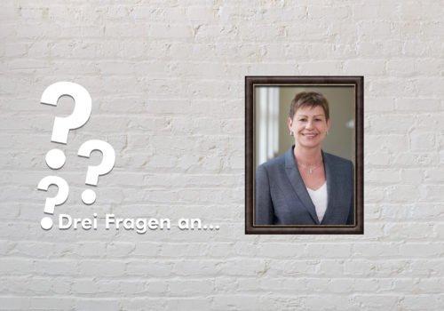 Fotomontage: Eine weiße Steinwand - darauf ein Rahmen, in den ein Bild von Elke Breitenbach montiert ist, daneben der Schriftzug Drei Fragen an... und drei Fragezeichen.