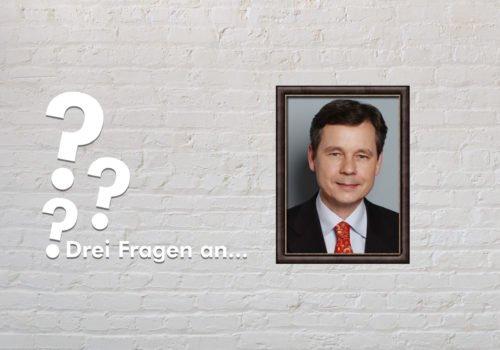 Fotomontage: Eine weiße Steinwand - darauf ein Rahmen, in den ein Bild von Uwe Brockhausen montiert ist, daneben der Schriftzug Drei Fragen an... und drei Fragezeichen.
