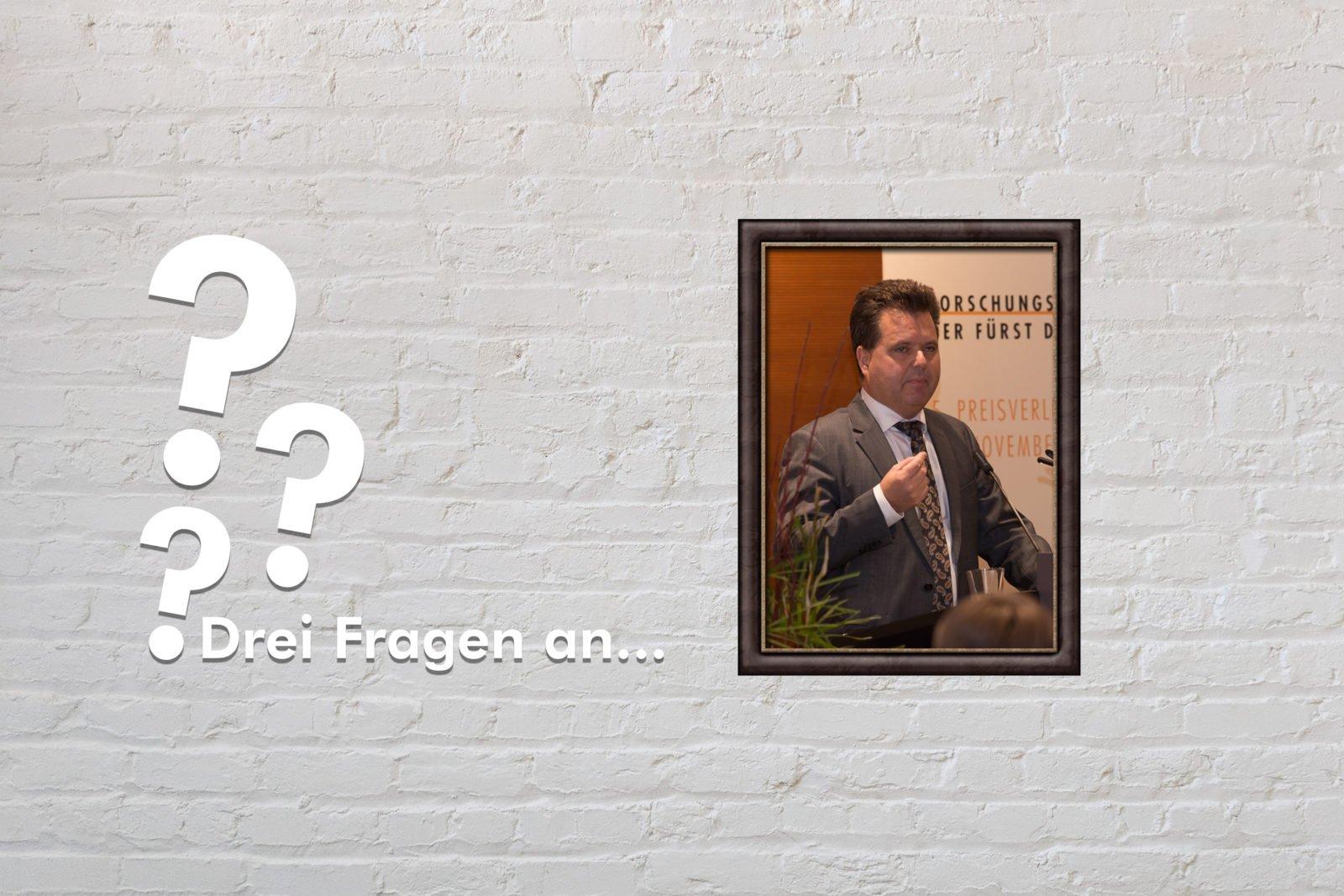 Fotomontage: Eine weiße Steinwand - darauf ein Rahmen, in den ein Bild von Jürgen Dusel montiert ist, daneben der Schriftzug Drei Fragen an... und drei Fragezeichen.