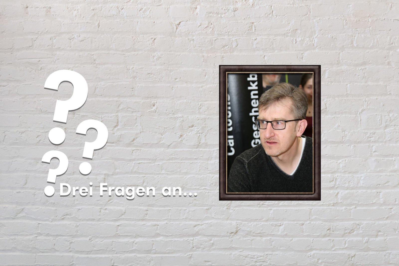Fotomontage: Eine weiße Steinwand - darauf ein Rahmen, in den ein Bild von Phil Hubbe montiert ist, daneben der Schriftzug Drei Fragen an... und drei Fragezeichen.