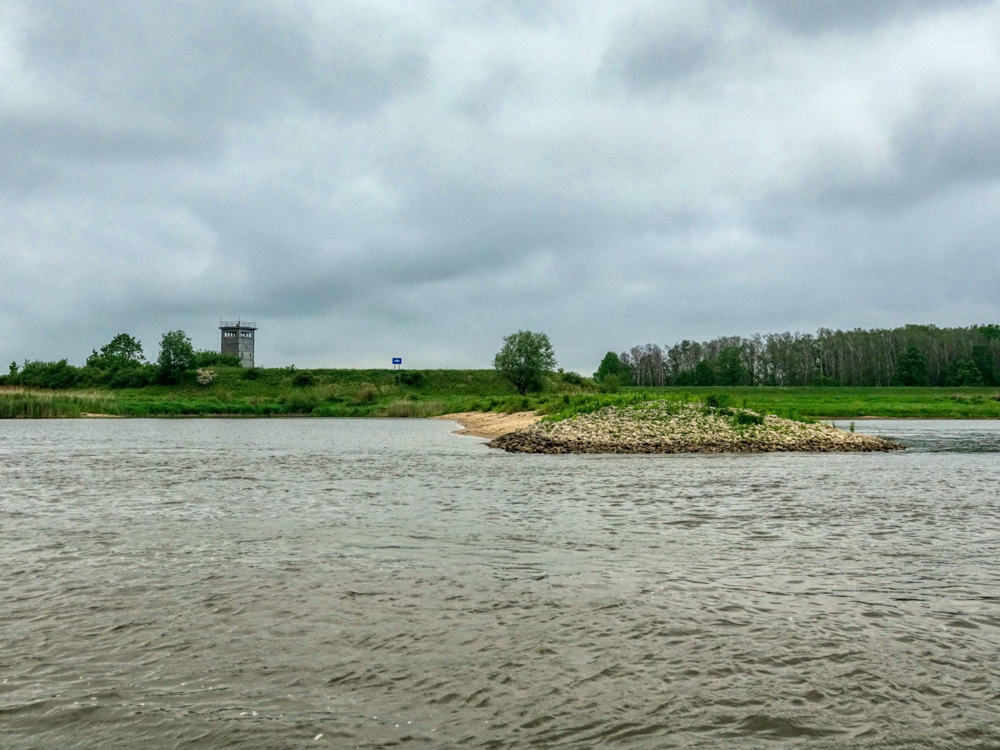 Vorne ist die Elbe zu sehen, im Hintergrund Gras und Bäume sowie ein alter Grenzwachturm.