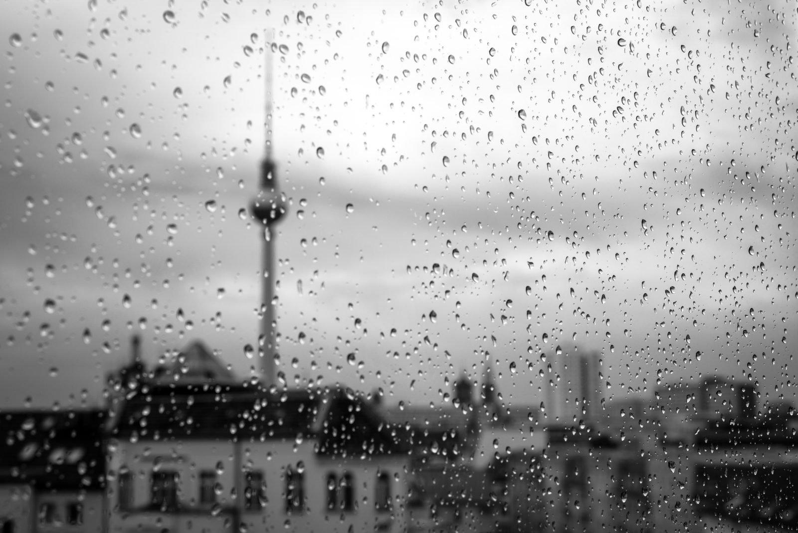 Regnerisches Wetter - Regentropfen laufen eine Fensterscheibe hinunter. Im Hintergrund ist der Berliner Fernsehturm zu sehen.