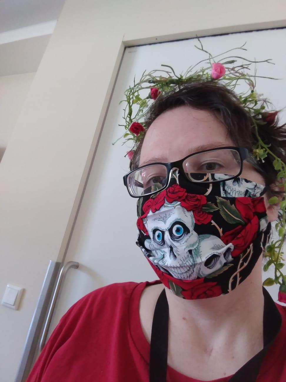 Bild von Freya Kettner, die einen rot-schwarzen Mundschutz mit Totenkopf-Motiv und in den Haaren Blumen trägt.
