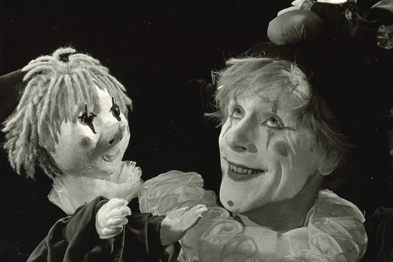 Ein geschminkter Clown mit einer Clown-Handpuppe. Scan eines Schwarzweißfotos.