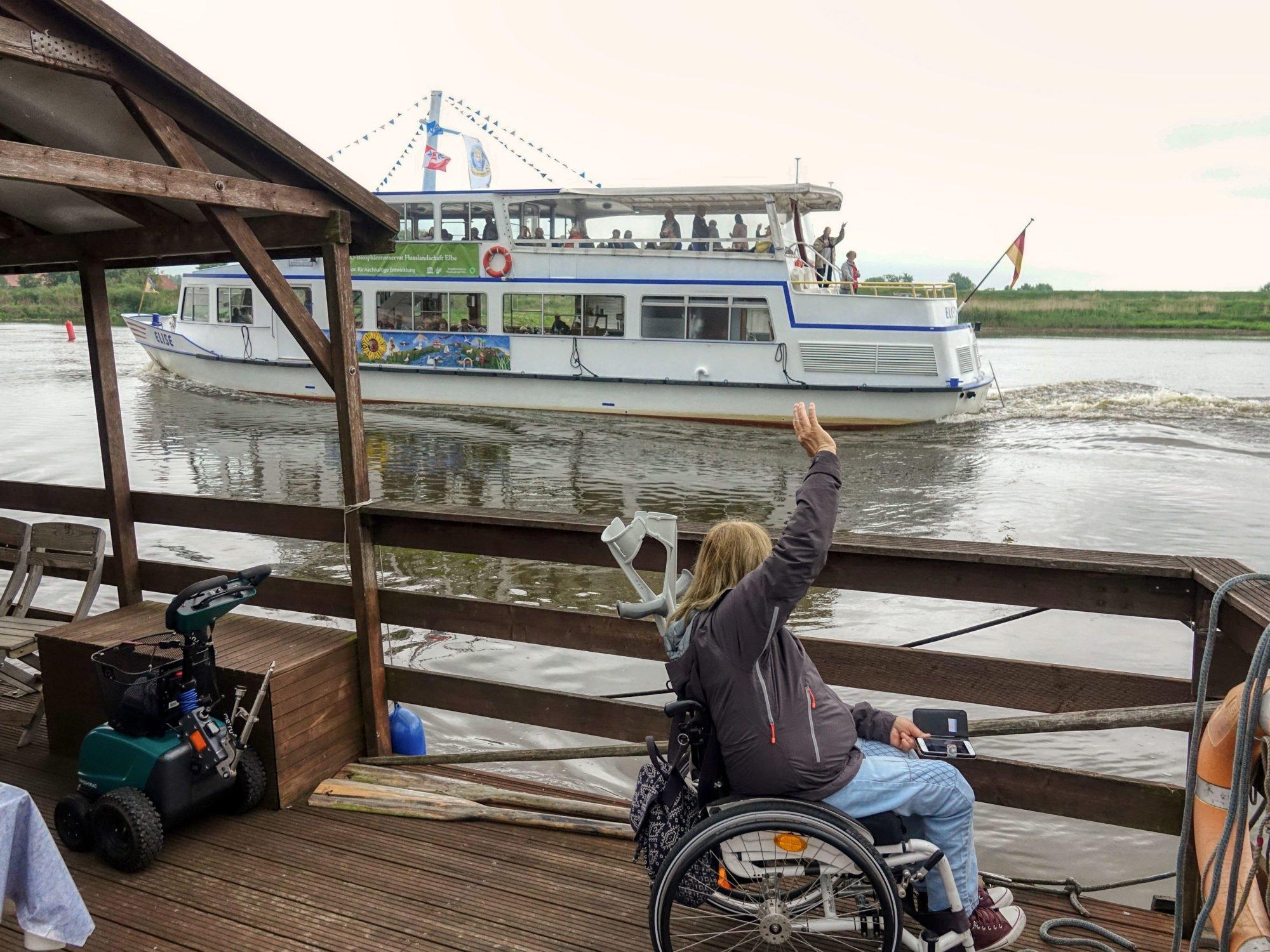 Petra Rosenberger steht mit ihrem Rollstuhl auf dem Floß und winkt den Passagieren eines vorbeifahrenden Passagierschiffes.