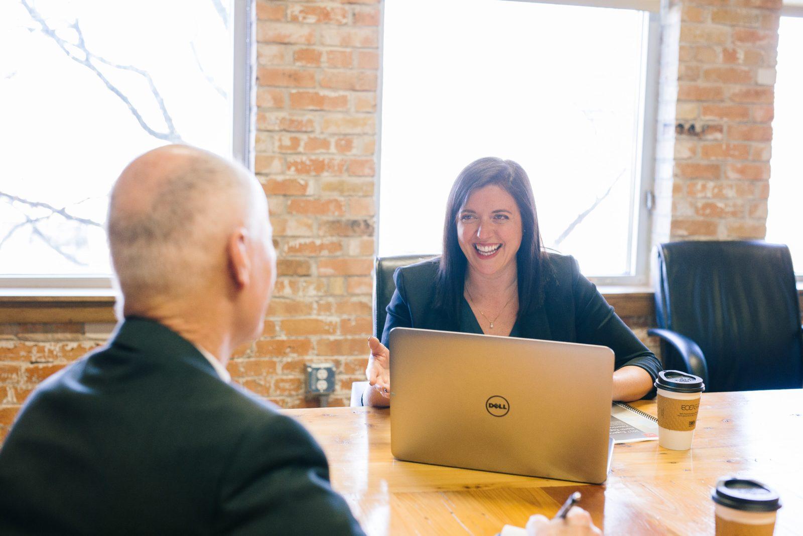 Eine berufliche Gesprächssituation. Ein älterer Herr von hinten sitzt einer Frau gegenüber, die lächelnd vor einem Laptop sitzt.