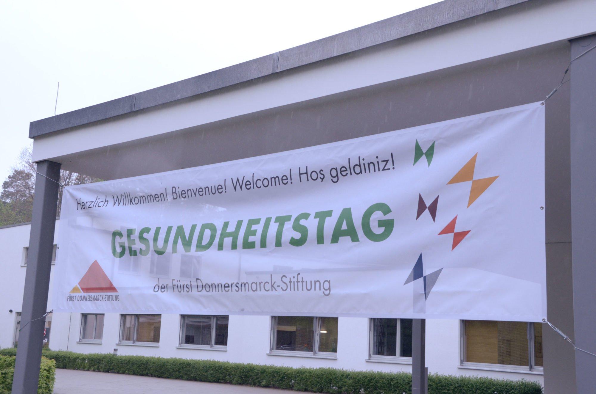 Zu sehen ist das Banner des Gesundheitstages, das vor dem P.A.N. Zentrum hängt. Es hat die Aufschrift Herzlich Willkommen! Gesundheitstag der Fürst Donnersmarck-Stiftung