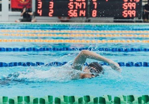 Stock-Foto: Ein junger Mann schwimmt bei einem Wettbewerb - Nahaufnahme, im Hintergrund sind Anzeigetafeln und Fotografen zu sehen.