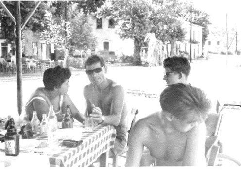 Scan einer Schwarzweißfotografie: drei Männer, alle oberkörperfrei und einer davon im Rollstuhl sitzend, und eine Frau sitzen gemeinsam an einem Tisch.