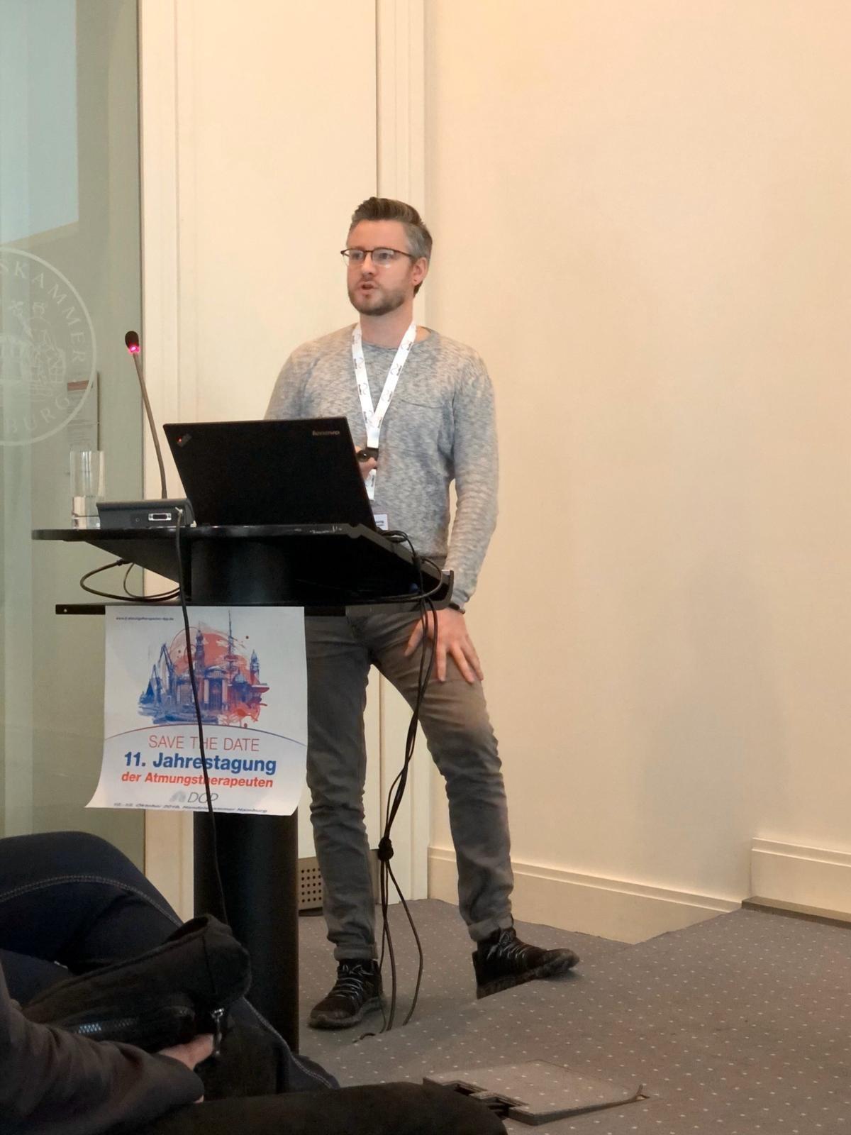 Philipp Gutschmidt hinter einem Rednerpult, auf dem das Logo des AT-Kongress zu sehen ist.