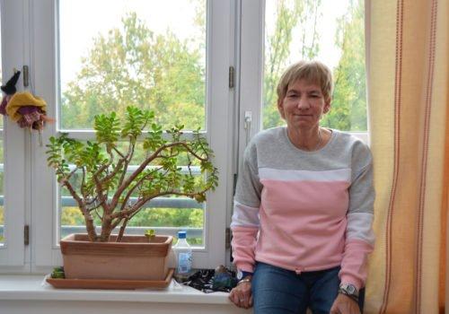 Barbara Hagedorn angelehnt an ihrer Fensterbank. Neben ihr eine Pflanze. Im Fenster hängt eine Hexe aus Stoff.