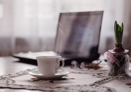 Ein Laptop und eine Tasse Kaffee auf einem Tisch mit Tischdecke.