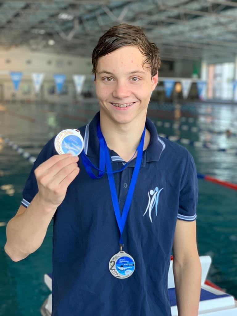 Jan Schreiber vor einem Schwimmbecken. Er hält eine Medaille in der Hand und lächelt in die Kamera.