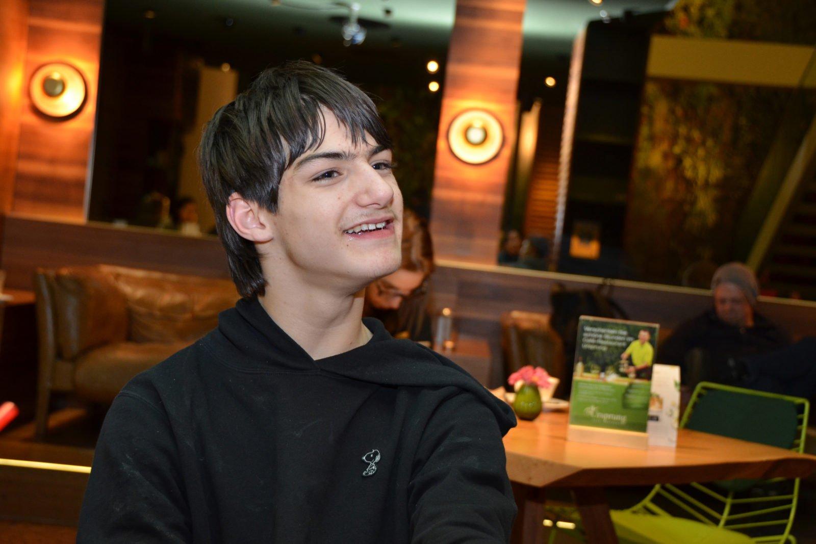 Linus Bade in einem Café - er lächelt und blickt leicht an der Kamera vorbei. Im Hintergrund sind Leute an Tischen zu erkennen, aber verschwommen.