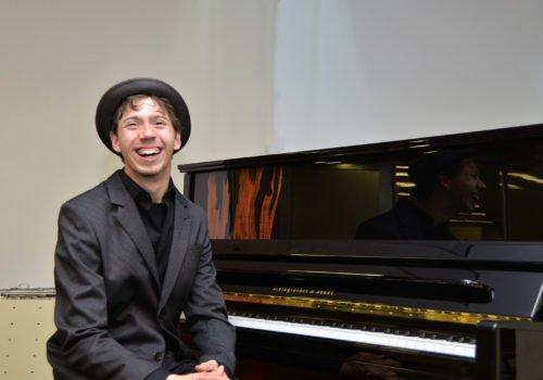 Junger Mann mit Hut sitzt vor einem Klavier und lacht in die Kamera