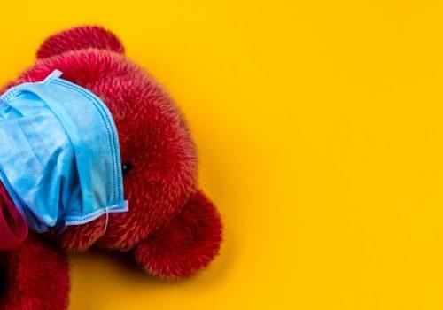 Ein roter Teddybär mit blauer OP-Maske auf gelben Hintergrund.