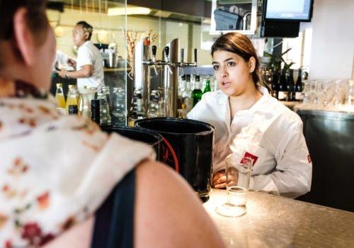 Eine junge Frau steht in einem Restaurant hinter der Bar und bedient einen Gast.