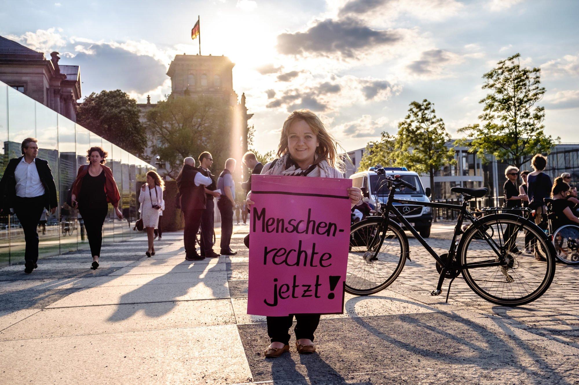 """Eine Frau mit Kleinwuchs demonstriert in Berlin, vor dem Bundestag. Sie hält ein Plakat in den Händen auf dem steht: """"Menschenrechte jetzt!""""."""
