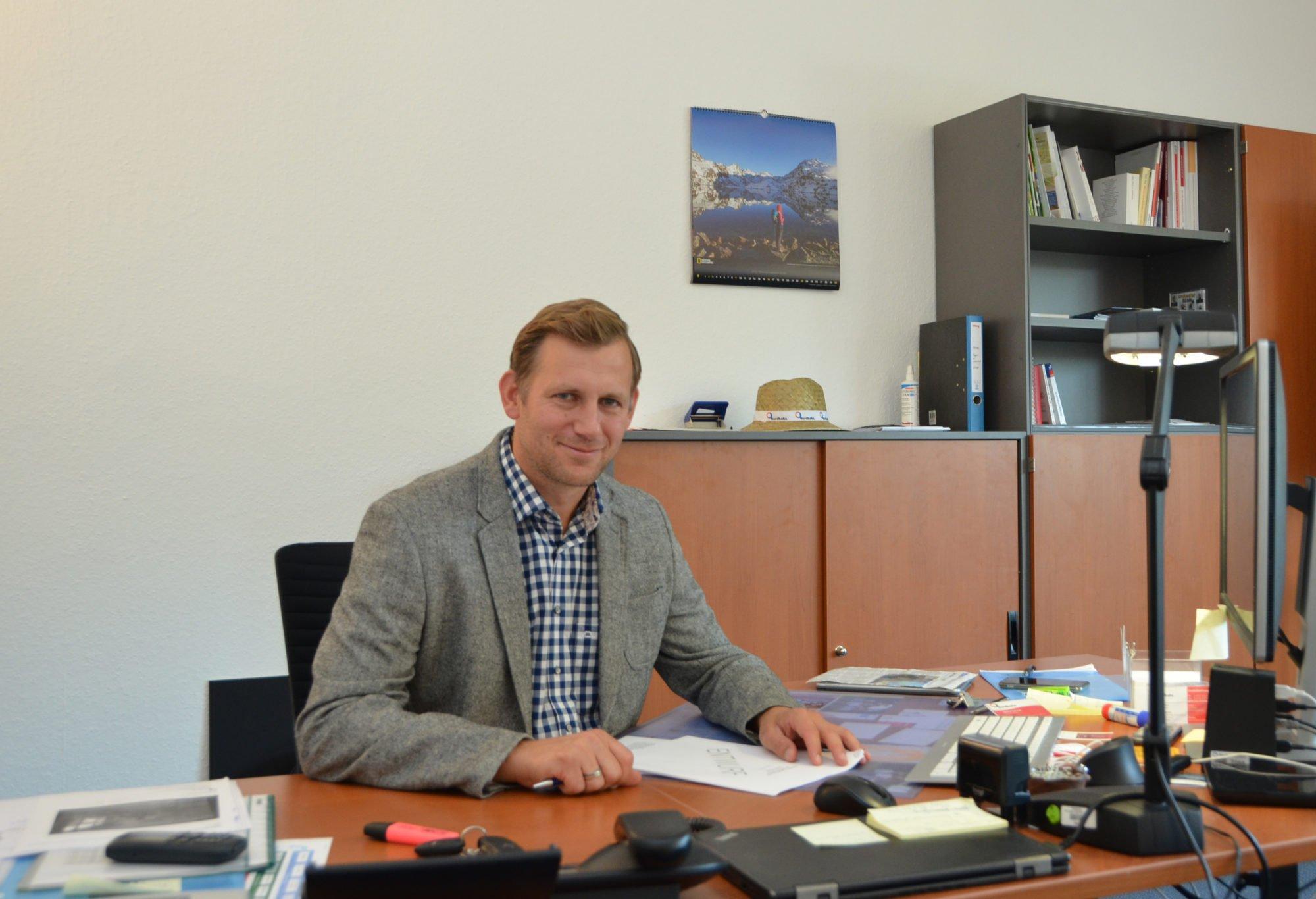 Micha Schaub sitzt an einem Schreibtisch und schaut lächelnd in die Kamera.