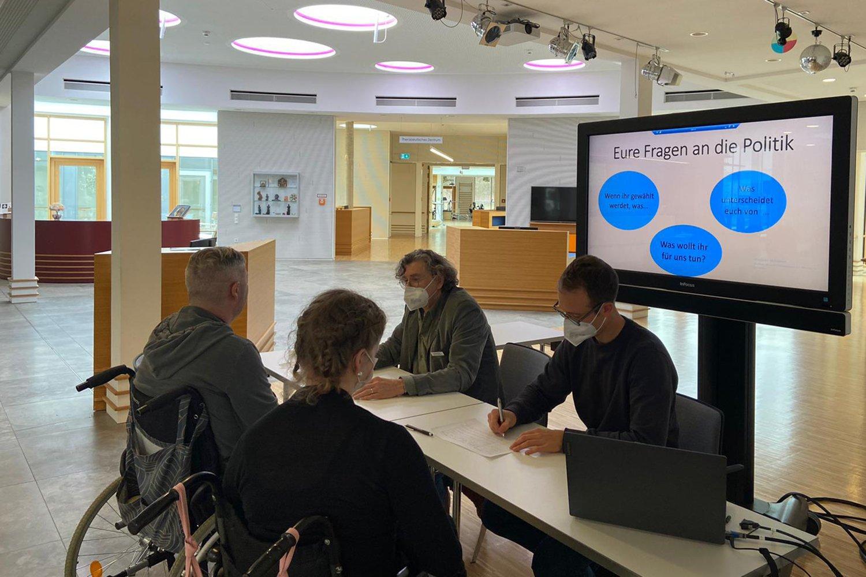 Eine Frau und ein Mann, beide im Rollstuhl, sitzen an einem Tisch mit zwei Mitarbeitenden der FDST. Im Hintergrund ein Bildschirm auf dem steht: Ihre Fragen an die Politik.