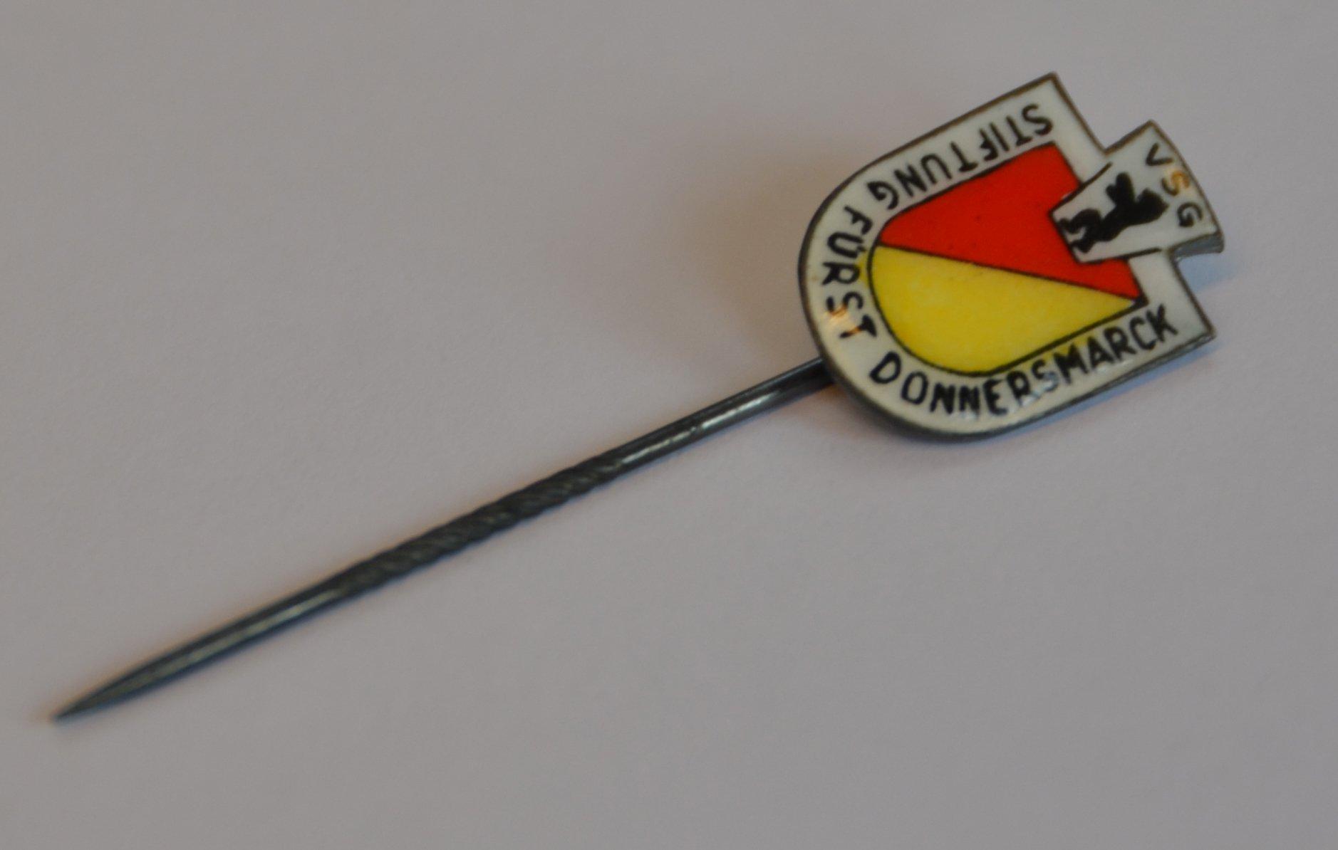 Eine Anstecknadel mit dem selben Logo des Abzeichens.