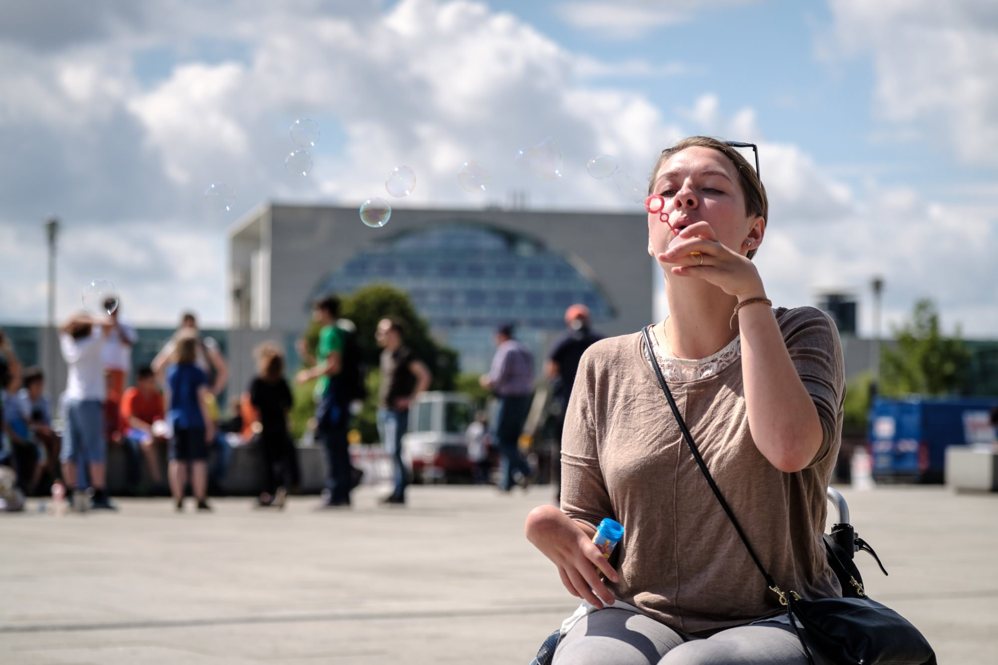 Junge Frau im Rollstuhl macht Seifenblasen. Es ist ein sonniger Tag, im Hintergrund sind Menschen verschwommen zu erkennen.