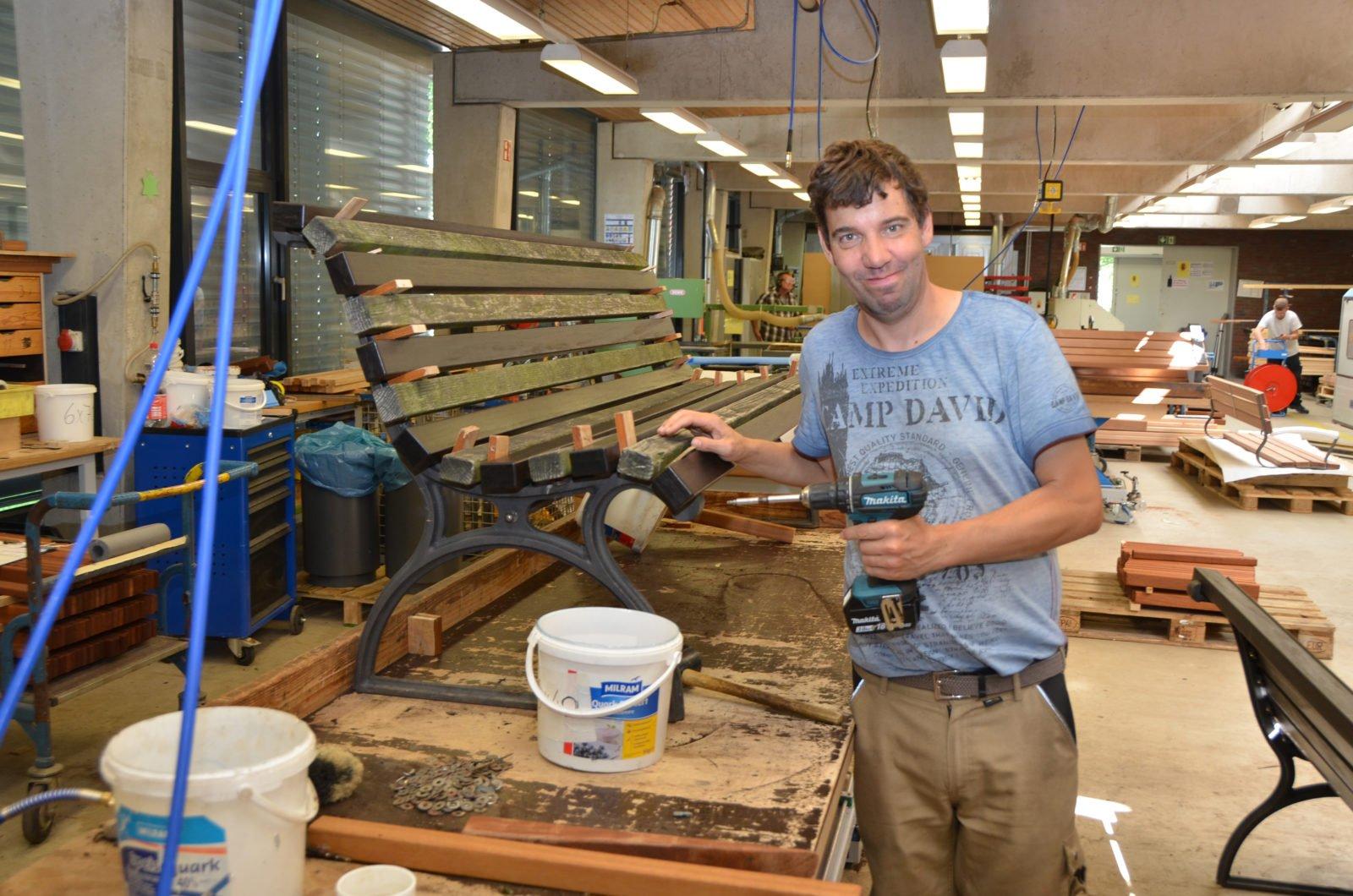 Ein Werkstattmitarbeiter steht mit einem Akkuschrauber in der Hand vor einer Parkbank, die restauriert werden soll.
