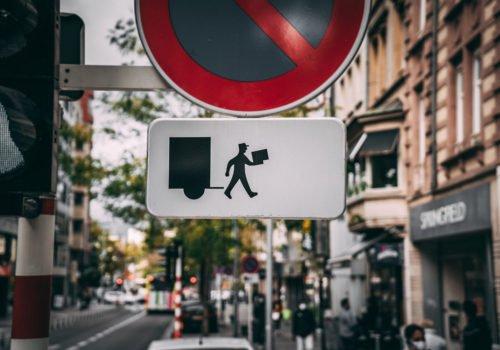 Ein Straßenschild für Halteverbot, darunter ein weißes Schild mit dem Piktogramm eines Paketboten, das symbolisiert, dass Paket- und Briefboten ausgenommen sind.