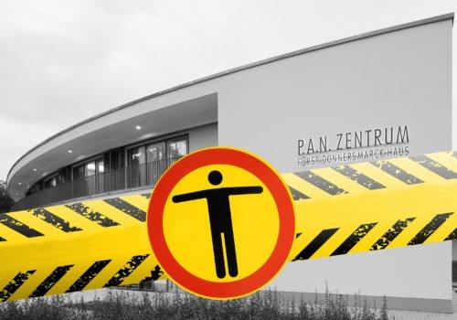 """Schwarz-Weiß-Bild des P.A.N.Zentrums - ins Bild montiert eine gelb-schwarzes Band und einem Piktogramm """"Zugang verboten"""""""
