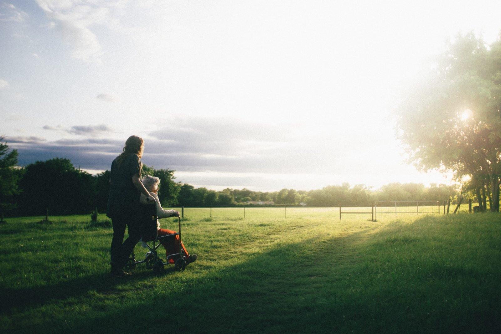 Zwei Menschen, von hinten fotografiert, auf einer grünen Wiese, eine Person im Rollstuhl, die andere dahinter - am Hoizont ist die wolkenbedeckte Sonne zu sehen.