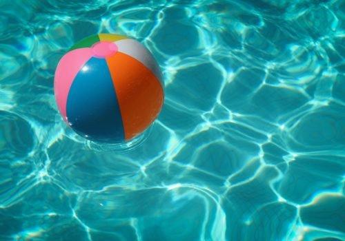 Ein bunter mit Luft gefüllter Plastikball schwimmt auf Wasser.