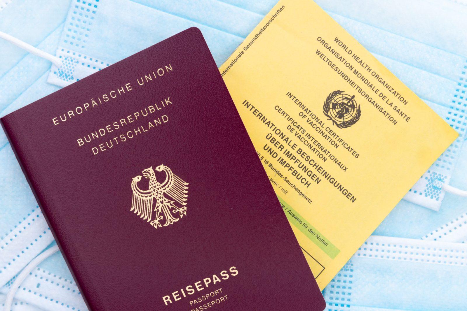 Ein deutscher Reisepass und ein Impfpass liegen auf einem Haufen OP-Masken.