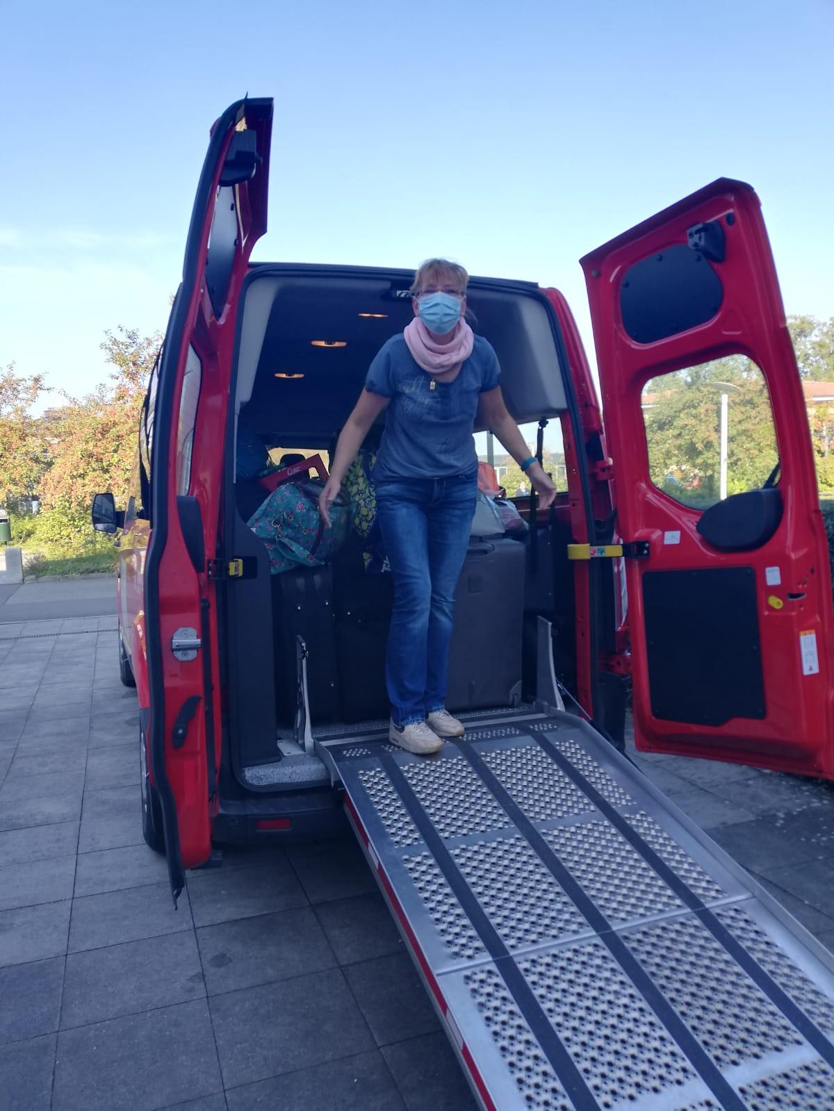 Michaela Ruhp, Alltagsmaske tragend, steht auf der Rollstuhlrampe eines Kleinbusses.