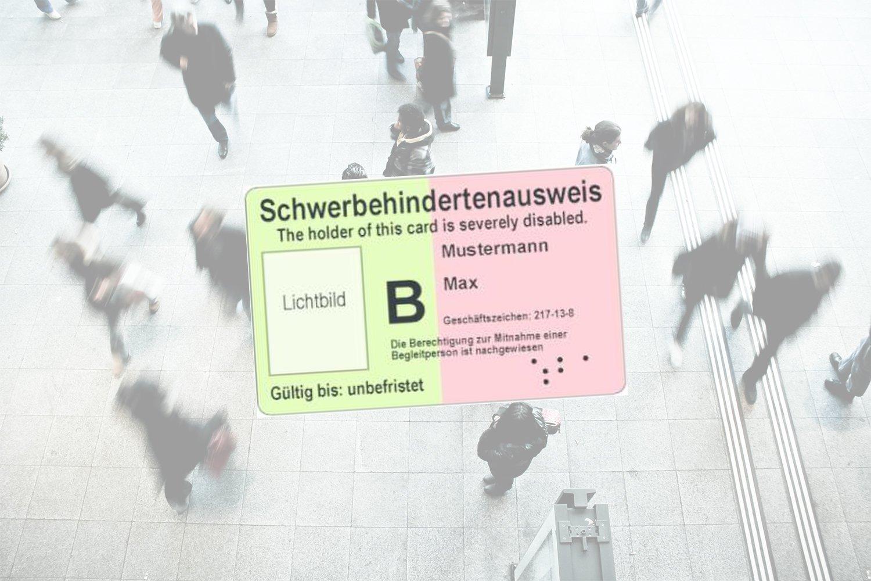 In der Mitte des Bildes das Muster eines Schwerbehindertenausweises. Im Hintergrund sind schemenhaft Menschen zu erkennen, die sich über einen Gehweg bewegen.