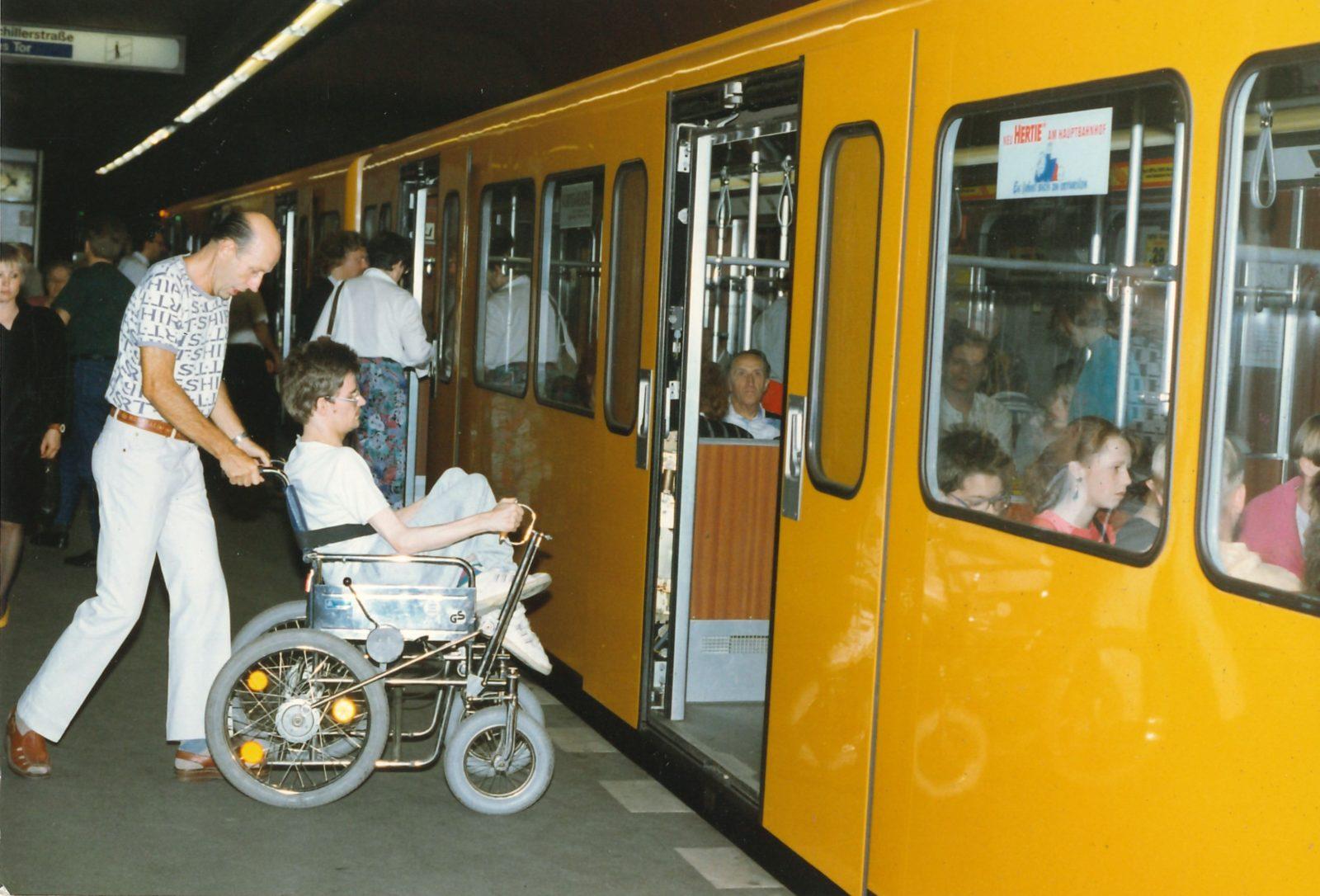 Ein altes Foto: Ein Mann hilft einem anderen Mann im Rollstuhl beim Einstieg in eine Berliner U-Bahn.