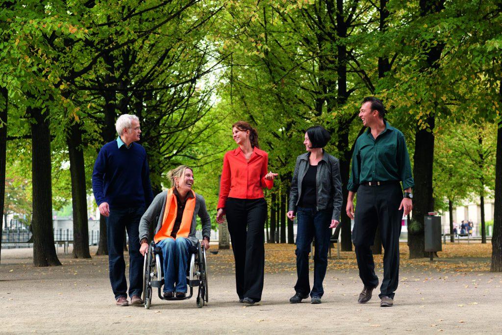 Eine Gruppe Menschen, inklusive Rollstuhlfahrerin, macht einen Spaziergang im Berliner Tiergarten bei Sonnenschein.