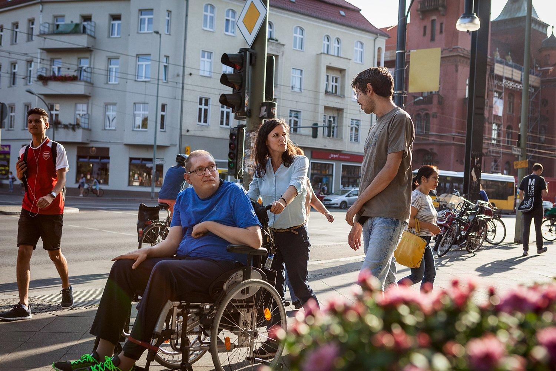 Zwei Männer, einer im Rollstuhl und einer zu Fuß, sind begleitet von einer jungen Frau in Berlin unterwegs. Alle sind gut gelaunt und lächeln.