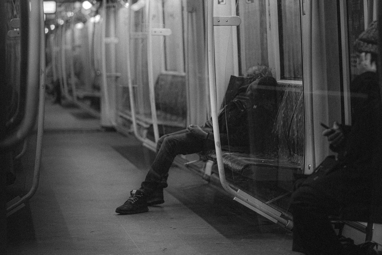 Schwarz-Weiß Foto aus der Berliner U-Bahn Ein Mann schläft auf der Sitzbank.
