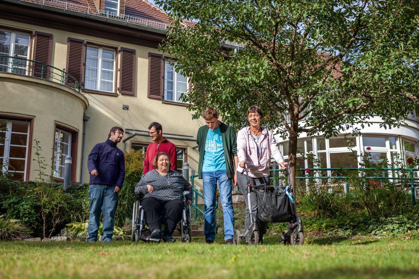 Drei Männer und zwei Frauen laufen durch den Garten der Villa Donnersmarck. Eine Frau sitzt im Rollstuhl, die andere benutzt einen Rollator.